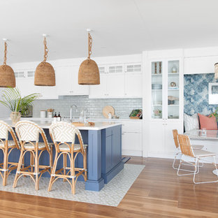 Large beach style l-shaped eat-in kitchen in Gold Coast - Tweed with shaker cabinets, white cabinets, with island, white benchtop, a single-bowl sink, quartz benchtops, green splashback, porcelain splashback, stainless steel appliances, porcelain floors and beige floor.