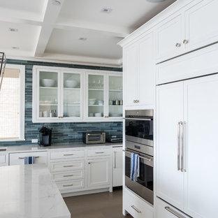 Foto di una cucina costiera di medie dimensioni con lavello sottopiano, ante di vetro, ante bianche, paraspruzzi blu, paraspruzzi con piastrelle di vetro, elettrodomestici in acciaio inossidabile, pavimento in legno massello medio, isola, pavimento marrone e top bianco