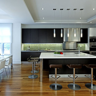 Large contemporary eat-in kitchen designs - Eat-in kitchen - large contemporary single-wall dark wood floor eat-in kitchen idea in Toronto with stainless steel appliances, an undermount sink, flat-panel cabinets, black cabinets, solid surface countertops, green backsplash, matchstick tile backsplash and an island