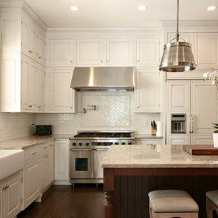 Imagen de cocina en L, tradicional, con fregadero sobremueble, electrodomésticos con paneles, armarios con paneles con relieve, puertas de armario blancas, encimera de mármol, salpicadero blanco y salpicadero de azulejos tipo metro