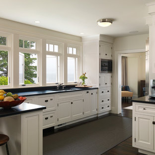 Kitchen - traditional l-shaped kitchen idea in Boston with an undermount sink, white cabinets and black backsplash