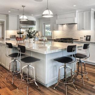オレンジカウンティの中くらいのトランジショナルスタイルのおしゃれなキッチン (白いキッチンパネル、アンダーカウンターシンク、落し込みパネル扉のキャビネット、白いキャビネット、シルバーの調理設備、無垢フローリング、サブウェイタイルのキッチンパネル、茶色い床、珪岩カウンター、白いキッチンカウンター) の写真