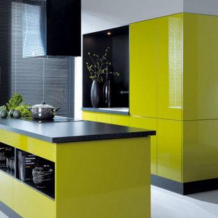 Modelo de cocina comedor lineal, moderna, grande, con fregadero encastrado, armarios con paneles lisos, puertas de armario amarillas, encimera de esteatita, electrodomésticos negros, suelo de cemento, una isla y suelo gris