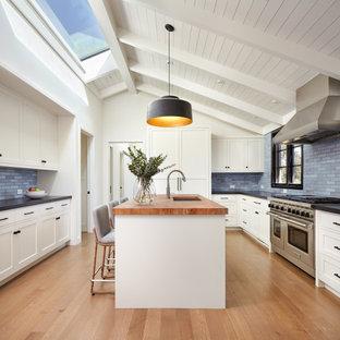 Exempel på ett avskilt klassiskt brun brunt u-kök, med en undermonterad diskho, skåp i shakerstil, vita skåp, träbänkskiva, blått stänkskydd, stänkskydd i tunnelbanekakel, integrerade vitvaror, mellanmörkt trägolv, en köksö och brunt golv