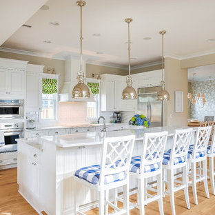 Inspiration for a mid-sized beach style light wood floor open concept kitchen remodel in Philadelphia with recessed-panel cabinets, white cabinets, quartz countertops, white backsplash, ceramic backsplash, stainless steel appliances and an island