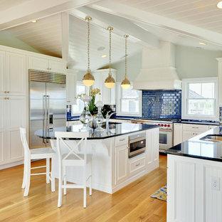 Ejemplo de cocina en U, marinera, con electrodomésticos de acero inoxidable, fregadero de doble seno, armarios con paneles empotrados, puertas de armario blancas, encimera de granito, salpicadero azul y salpicadero de azulejos tipo metro
