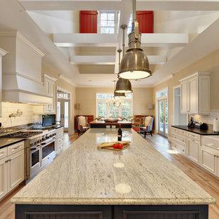 Ejemplo de cocina comedor marinera con electrodomésticos de acero inoxidable, salpicadero de azulejos tipo metro, fregadero sobremueble, encimera de granito, armarios con paneles empotrados, puertas de armario blancas, salpicadero blanco y encimeras negras