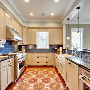 Moderne Küche in U-Form mit Schrankfronten im Shaker-Stil, Küchengeräten aus Edelstahl, Granit-Arbeitsplatte, Landhausspüle, beigen Schränken, Küchenrückwand in Blau und Rückwand aus Metrofliesen in Philadelphia