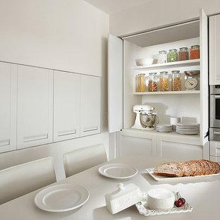 他の地域のコンテンポラリースタイルのおしゃれなキッチン (シェーカースタイル扉のキャビネット、白いキャビネット、シルバーの調理設備) の写真