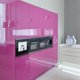 Moderne Küche mit flächenbündigen Schrankfronten und schwarzen Elektrogeräten in Sonstige