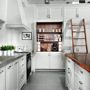 Moderne Küche mit Edelstahl-Arbeitsplatte, schwarzen Elektrogeräten, Schrankfronten im Shaker-Stil und weißen Schränken in Sonstige