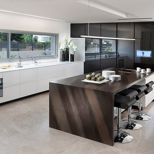 Modern kitchen designs - Example of a minimalist l-shaped kitchen design in Other with flat-panel cabinets, black cabinets, black appliances and granite countertops