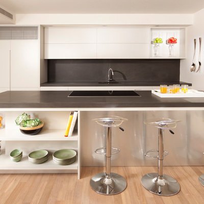 Kitchen - modern galley kitchen idea in Other with flat-panel cabinets, white cabinets, gray backsplash and paneled appliances