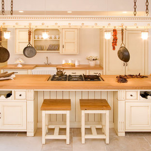 Inspiration for a farmhouse galley kitchen remodel in Other with wood countertops, a farmhouse sink, recessed-panel cabinets and beige cabinets