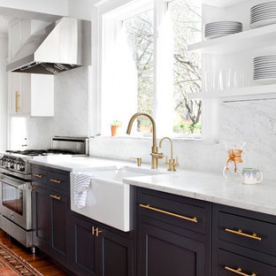 Ejemplo de cocina tradicional renovada con fregadero sobremueble, armarios estilo shaker, puertas de armario negras, encimera de mármol, electrodomésticos de acero inoxidable, suelo de madera en tonos medios, salpicadero de mármol y encimeras blancas