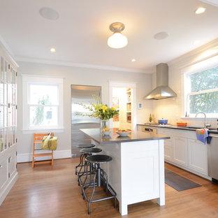 Modern inredning av ett kök, med stänkskydd i tunnelbanekakel, luckor med glaspanel, vita skåp, rostfria vitvaror, vitt stänkskydd och en undermonterad diskho