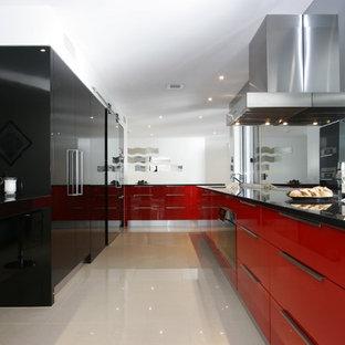 Exempel på ett modernt parallellkök, med släta luckor och röda skåp