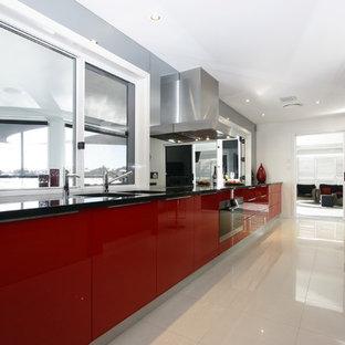 Imagen de cocina de galera, minimalista, con puertas de armario rojas