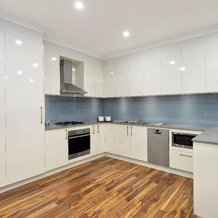 シドニーのカントリー風おしゃれなキッチン (ダブルシンク、フラットパネル扉のキャビネット、白いキャビネット、クオーツストーンカウンター、青いキッチンパネル、ガラス板のキッチンパネル、シルバーの調理設備の、無垢フローリング、グレーのキッチンカウンター) の写真