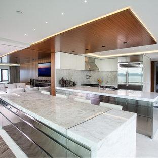 Immagine di una grande cucina moderna con lavello sottopiano, ante lisce, ante in acciaio inossidabile, top in quarzite, paraspruzzi bianco, paraspruzzi in lastra di pietra, elettrodomestici in acciaio inossidabile e pavimento in pietra calcarea