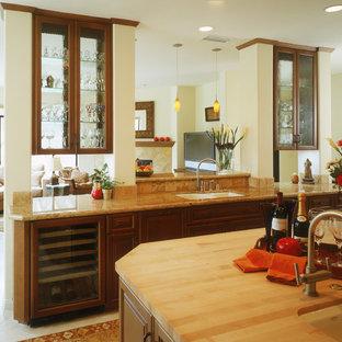 Offene Klassische Küche mit Glasfronten, Arbeitsplatte aus Holz, Doppelwaschbecken, dunklen Holzschränken, Küchenrückwand in Beige, Rückwand aus Keramikfliesen, Keramikboden, Kücheninsel und weißem Boden in San Diego