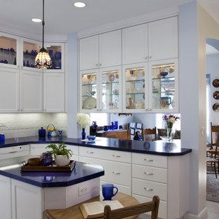 サンディエゴの中サイズのエクレクティックスタイルのおしゃれなキッチン (ガラス扉のキャビネット、アンダーカウンターシンク、白いキャビネット、人工大理石カウンター、白いキッチンパネル、磁器タイルのキッチンパネル、パネルと同色の調理設備、セラミックタイルの床、白い床、青いキッチンカウンター) の写真