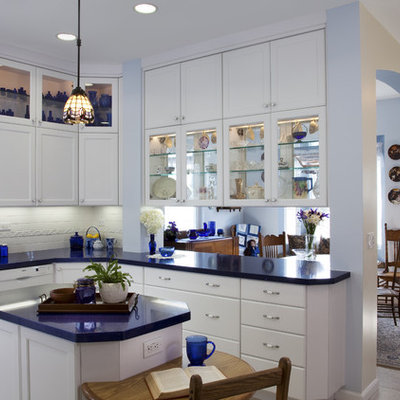 Example of a mid-sized eclectic u-shaped ceramic tile and white floor enclosed kitchen design in San Diego with glass-front cabinets, an undermount sink, white cabinets, solid surface countertops, white backsplash, porcelain backsplash, paneled appliances, an island and blue countertops