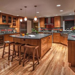 シアトルの広いトラディショナルスタイルのおしゃれなキッチン (エプロンフロントシンク、ソープストーンカウンター、シェーカースタイル扉のキャビネット、中間色木目調キャビネット、赤いキッチンパネル、セラミックタイルのキッチンパネル、シルバーの調理設備、無垢フローリング、茶色い床) の写真