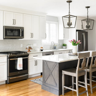 Mid-sized transitional eat-in kitchen remodeling - Inspiration for a mid-sized transitional galley brown floor eat-in kitchen remodel in Boston with an island, an undermount sink, shaker cabinets, white cabinets, gray backsplash, stainless steel appliances and gray countertops