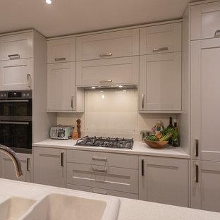 ロンドンの中サイズのエクレクティックスタイルのおしゃれなキッチン (シングルシンク、シェーカースタイル扉のキャビネット、グレーのキャビネット、人工大理石カウンター、ガラス板のキッチンパネル、パネルと同色の調理設備、無垢フローリング、白いキッチンカウンター) の写真