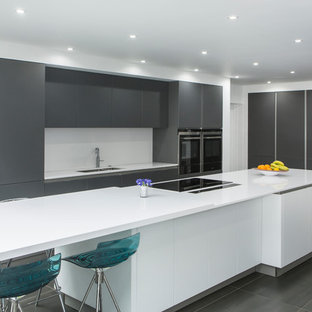 Large contemporary single-wall open plan kitchen in Essex with an integrated sink, flat-panel cabinets, grey cabinets, quartzite benchtops, white splashback, stone slab splashback, stainless steel appliances, porcelain floors and with island.
