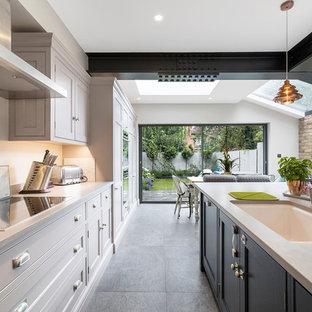 Immagine di una cucina contemporanea di medie dimensioni con lavello integrato, ante in stile shaker, ante grigie, top in cemento, paraspruzzi bianco, elettrodomestici in acciaio inossidabile, pavimento in cemento, isola e pavimento grigio