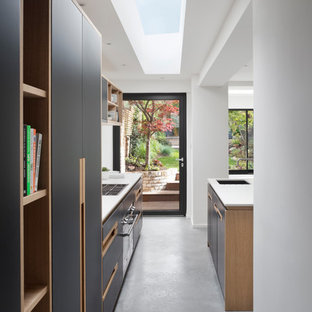 Design ideas for a medium sized contemporary galley kitchen/diner in London with a built-in sink, flat-panel cabinets, blue cabinets, composite countertops, white splashback, concrete flooring, an island, grey floors and white worktops.