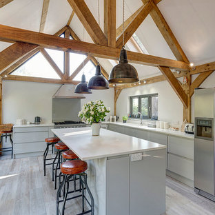 Design ideas for a farmhouse l-shaped kitchen in Kent with a double-bowl sink, flat-panel cabinets, grey cabinets, stainless steel appliances, an island and grey floors.