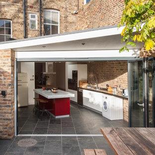 Неиссякаемый источник вдохновения для домашнего уюта: маленькая отдельная кухня в современном стиле с плоскими фасадами, белыми фасадами, полом из сланца, островом и серым полом