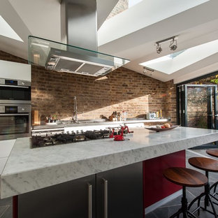 This is an example of a mid-sized contemporary single-wall eat-in kitchen in London with an integrated sink, flat-panel cabinets, white cabinets, marble benchtops, stainless steel appliances, ceramic floors and with island.