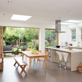Foto di una cucina abitabile contemporanea di medie dimensioni con lavello sottopiano, ante lisce, ante grigie, top in superficie solida, pavimento con piastrelle in ceramica e isola