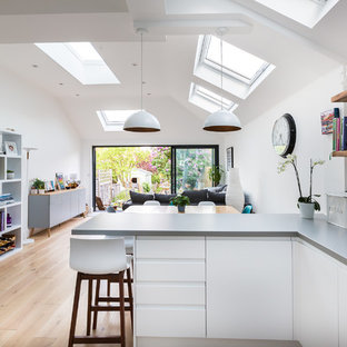 Photo of a contemporary l-shaped open plan kitchen in Essex with flat-panel cabinets, white cabinets, white splashback, light hardwood flooring, a breakfast bar, beige floors and grey worktops.