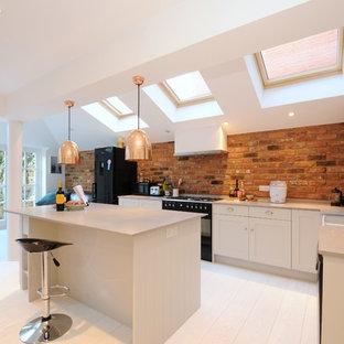 ロンドンの北欧スタイルのおしゃれなキッチン (エプロンフロントシンク、シェーカースタイル扉のキャビネット、白いキャビネット、黒い調理設備、淡色無垢フローリング) の写真