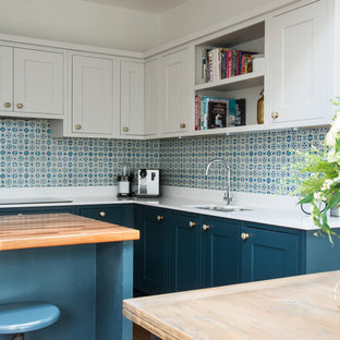 エディンバラの中くらいのトラディショナルスタイルのおしゃれなキッチン (シェーカースタイル扉のキャビネット、青いキャビネット、セラミックタイルのキッチンパネル、アンダーカウンターシンク、人工大理石カウンター、白いキッチンパネル、濃色無垢フローリング) の写真