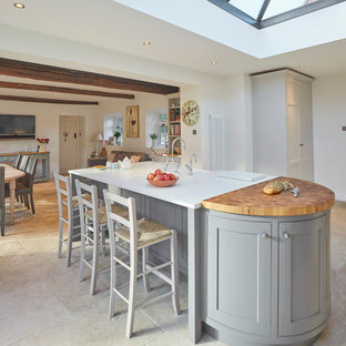 Design ideas for a large country kitchen/diner in Wiltshire with a belfast sink, recessed-panel cabinets, grey cabinets, engineered stone countertops, beige splashback, stone slab splashback, stainless steel appliances, limestone flooring and a breakfast bar.