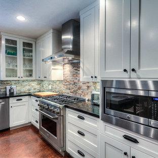 ヒューストンの中サイズのインダストリアルスタイルのおしゃれなキッチン (落し込みパネル扉のキャビネット、白いキャビネット、御影石カウンター、マルチカラーのキッチンパネル、シルバーの調理設備、アンダーカウンターシンク、ボーダータイルのキッチンパネル、コンクリートの床、茶色い床) の写真