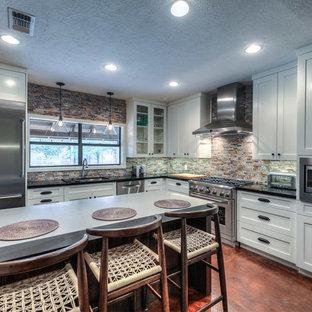 ヒューストンの中サイズのインダストリアルスタイルのおしゃれなキッチン (落し込みパネル扉のキャビネット、白いキャビネット、御影石カウンター、マルチカラーのキッチンパネル、シルバーの調理設備の、アンダーカウンターシンク、ボーダータイルのキッチンパネル、コンクリートの床、茶色い床) の写真