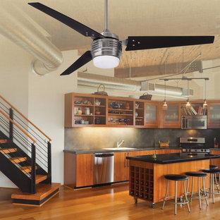 他の地域の中サイズのインダストリアルスタイルのおしゃれなキッチン (アンダーカウンターシンク、フラットパネル扉のキャビネット、中間色木目調キャビネット、御影石カウンター、黒いキッチンパネル、セメントタイルのキッチンパネル、シルバーの調理設備の、淡色無垢フローリング) の写真