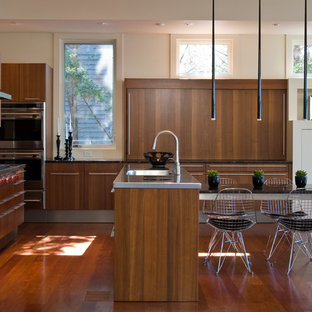 Example of a mid-sized trendy u-shaped medium tone wood floor eat-in kitchen design in Baltimore with an integrated sink, flat-panel cabinets, dark wood cabinets, stainless steel countertops, stainless steel appliances and an island