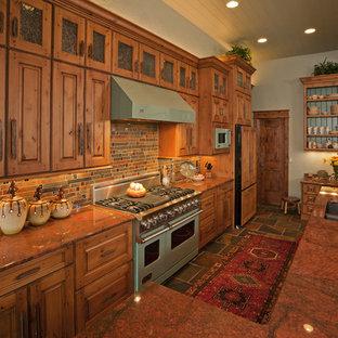 Idées déco pour une grand cuisine ouverte montagne en L avec un placard avec porte à panneau surélevé, des portes de placard en bois brun, un évier encastré, un plan de travail en granite, une crédence multicolore, un électroménager de couleur, un sol en ardoise, un îlot central, une crédence en ardoise et un sol multicolore.