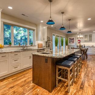 Klassische Wohnküche mit Unterbauwaschbecken, Schrankfronten im Shaker-Stil, weißen Schränken, Granit-Arbeitsplatte, Küchenrückwand in Weiß, Rückwand aus Metrofliesen, Küchengeräten aus Edelstahl, Kücheninsel und grauer Arbeitsplatte in Sonstige