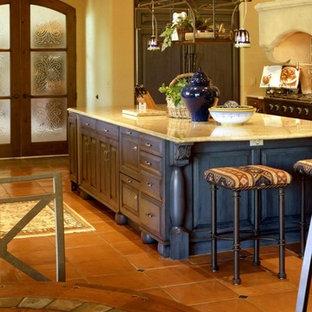 フェニックスのサンタフェスタイルのおしゃれなキッチン (アンダーカウンターシンク、インセット扉のキャビネット、緑のキャビネット、大理石カウンター、ベージュキッチンパネル、セラミックタイルのキッチンパネル、黒い調理設備、スレートの床) の写真