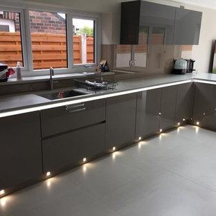 ロンドンの広いモダンスタイルのおしゃれなキッチン (ドロップインシンク、フラットパネル扉のキャビネット、紫のキャビネット、コンクリートカウンター、茶色いキッチンパネル、ガラスタイルのキッチンパネル、シルバーの調理設備、セラミックタイルの床、グレーの床、紫のキッチンカウンター) の写真