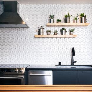 サンフランシスコの小さいコンテンポラリースタイルのおしゃれなII型キッチン (アンダーカウンターシンク、フラットパネル扉のキャビネット、黒いキャビネット、珪岩カウンター、白いキッチンパネル、セラミックタイルのキッチンパネル、シルバーの調理設備、コンクリートの床、グレーの床、黒いキッチンカウンター) の写真